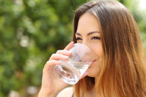 Happy healthy woman drinking fresh water from a glass outdoor with a green background