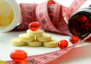 Measuring tape and bottle with pills. supplements of weight loss