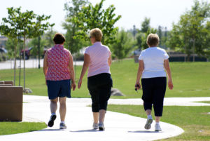 Three older women take a healthy walk through the park